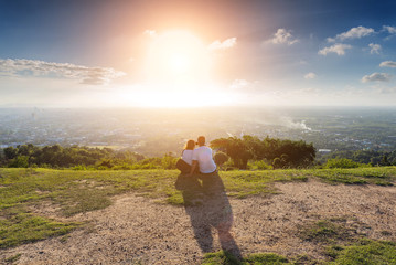 Romantic of couple love sitting on the cliff looking sunset at mountain, take a selfie.