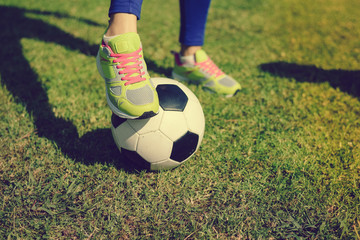 Close up view of player legs and ball on green grass outdoors background