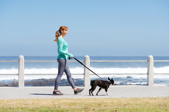 fit woman smiling and walking dog on path by sea