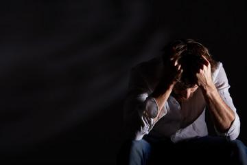 Schizophrenic man holding his head