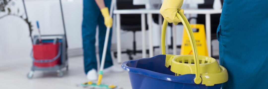 Cleaner is holding a bucket