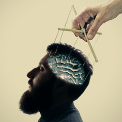 Concept manipulation of consciousness. Image of a hand, that manipulates the mind of man.
