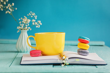 Big yellow cup of tea with flower and macaroons and notebook on blue background