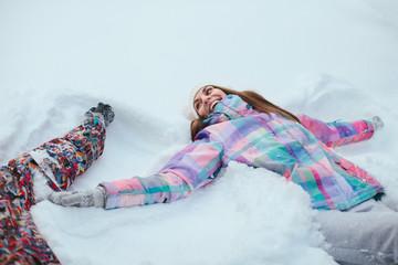 woman lying in snow making snow angel
