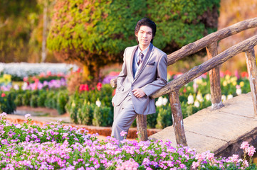 Handsome Groom Stand and Leaning at Wood Bridge in Park