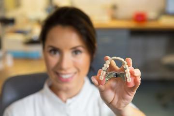 Dental technician presenting dental prosthesis in lab