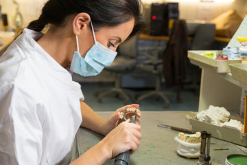 Technician in dental lab working on an implant with grinder
