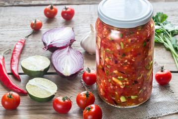 Jar of salsa with ingredients