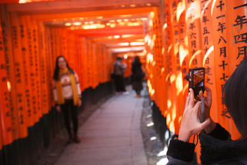 Tourists take pictures in the memory of the red torii gate at Fushimi Inari in Kyoto, Japan. At the gates of Buddhist sutras, the sacred texts.