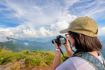 Hiker asian teens girl with backpack looking photo on digital camera is beautiful landscape natural of sierra and sky during sunset on mountain at Phu Chi Fa Forest Park, Chiang Rai, Thailand