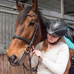 Junge Reiterin befestigt das Zaumzeug am Pferd - einen Hannoveraner