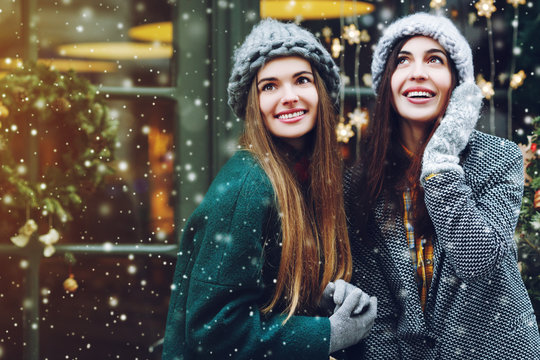 Outdoor waist up portrait of two young beautiful fashionable happy smiling girls posing on street. Models looking up, wearing stylish winter clothes. Snowfall, christmas background. Copy, empty space