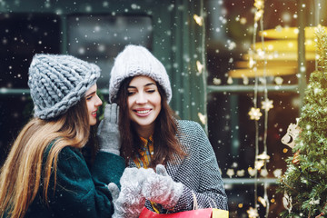 Outdoor portrait of two young beautiful fashionable girls posing with colorful shopping bags. Woman whispering to her smiling friend. Ladies wearing stylish winter hats. Christmas background, snowfall