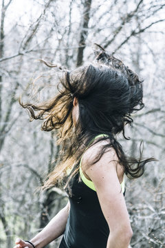 Beautiful young woman in nature with the hair in the air.