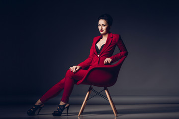 Attractive business woman. Portrait of a sexy young business lady in a red suit on a dark background