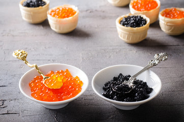 Black and red caviar tartlets, appetizer canapes in white bowls
