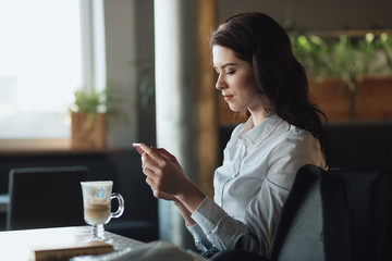 Business woman reading news on smart phone using app drinking latte in cafe