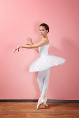 Young beautiful ballerina on wall background