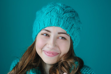 beautiful young woman in knitted hat posing in studio