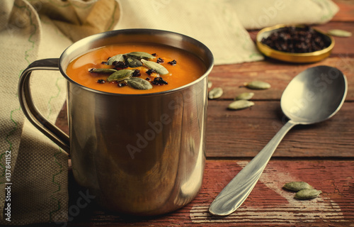 """Roasted pumpkin soup in metal mug with seeds and smoked ..."