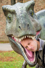 Belgrade, Serbia - October 05, 2014: Young man put his head into the mouth of a dinosaur in the dino park, Belgrade, Serbia