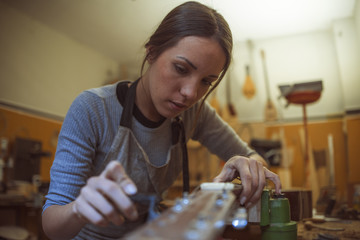 woman luthier is tuning a classic guitar in her musical instrument workshop