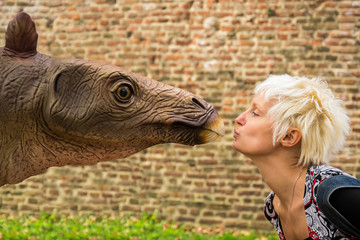 Belgrade, Serbia - October 05, 2014: Young woman kissing dinosaurs in the dino park, Belgrade, Serbia