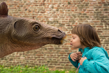 Belgrade, Serbia - October 05, 2014: Little child kissing dinosaurs in the dino park, Belgrade, Serbia
