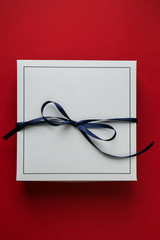 Single white gift paper box with blue ribbon bow, isolated on blue background