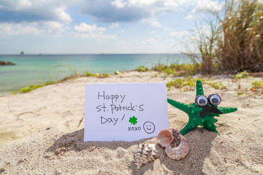 Green starfish with Happy St. Patrick day card at the beach.