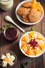 A light breakfast of cereal, jam, milk, biscuits and fruit. Wooden background. Top view. Close-up