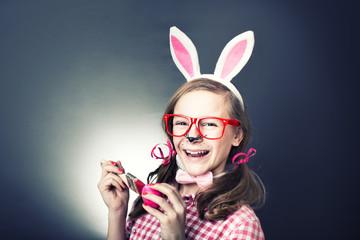 Kind mit Hasenohren malt mit Pinsel Eier an