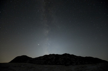 View of silhouetted mountains against starry sky