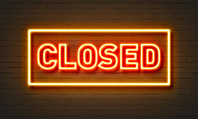 Closed neon sign on brick wall background.