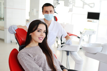 beautiful young girl smiling on the background of the dentist. dentist examines teeth attractive girl.