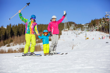 Cheerful family of three standing on ski slope