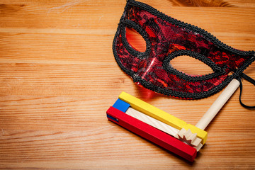 Judaism and religious holiday with wooden noisemaker or gragger (a traditional toy) for purim celebration holiday (jewish holiday) and a red mask on wooden background