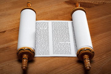 Judaism and religious text concept with a open Torah on wooden background