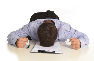 businessman sitting at office desk with hands on his head crying devastated and frustrated