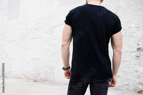 young muscular bearded man wearing black tshirt and jeans posing in