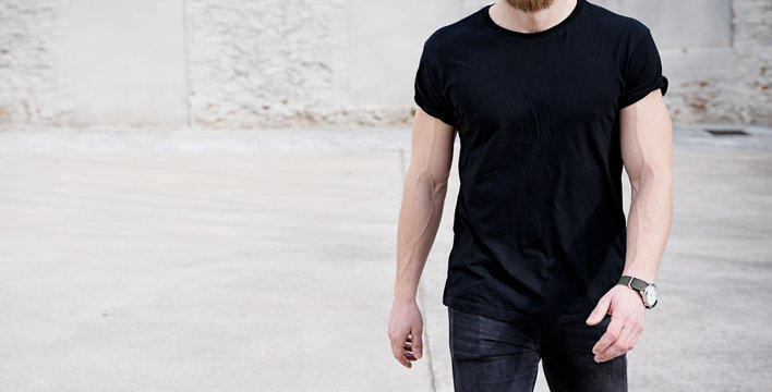 Young muscular man wearing black tshirt and jeans walking on the urban district. Blurred background. Hotizontal wide mockup.