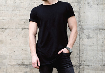 Closeup view of young bearded man wearing black tshirt and jeans posing in center of modern city. Empty concrete wall on the background. Hotizontal mockup.
