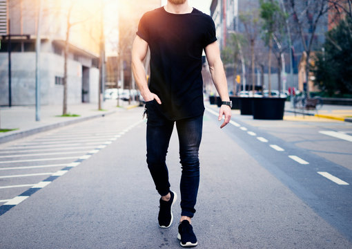 Young muscular man wearing black tshirt and jeans walking on the streets of the modern city. Blurred background. Hotizontal mockup.