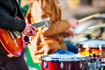 Festival music band. Hands playing on percussion instruments in city park . Drums with sticks closeup. Body part of male musicians. Sharpen is guitar and man hand.