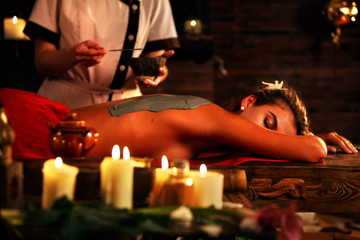 Mud mask of woman in spa salon. Back massage with clay full body . Girl on interior with candles foreground in oriental therapy room. Female lying on wooden spa bed. Beautician used cosmetic brush and