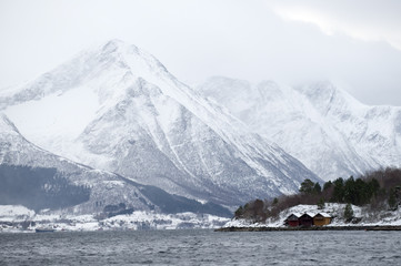 Snow covered mountains in fjord, Moere coastline, Norway, February 2009