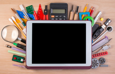 Tablet PC over school supplies or office supplies on school table. Background with school or office...