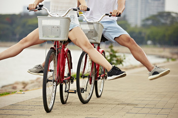 young couple having fun with bicycles in park