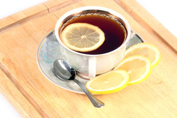 Morning porcelain cup of hot tea with a slice of lemon on a wooden tray