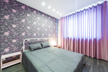 Interior bedroom with a large double bed with bedside tables,window on a background of modern wallpaper